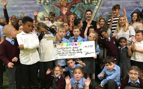 Lower Sixth Formers on a Social Studies course at the Shewsy handed over a cheque for £2,000 raised at the Salopian Postcard Art Exhibition