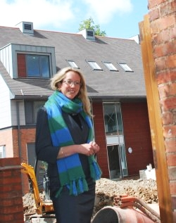 Kait Weston, wearing her EDH scarf, in front of the building site of Emma Darwin Hall